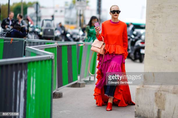 A guest wears an orange pink ruffle dress outside Giambattista Valli during Paris Fashion Week Womenswear Spring/Summer 2018 on October 2 2017 in...