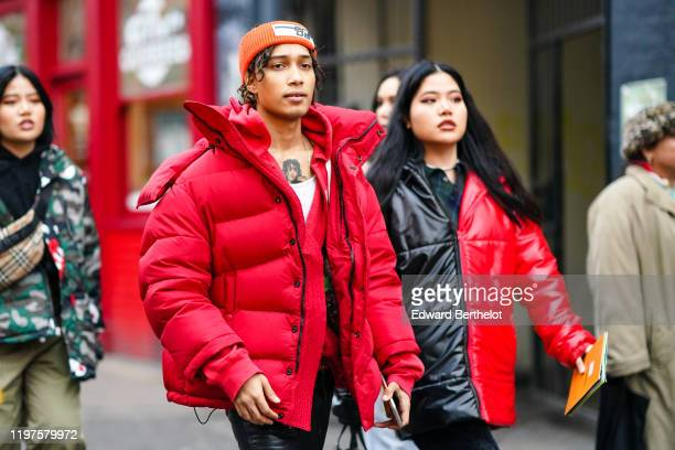 A guest wears an orange Prada elastic wool bandanna a red puffer jacket a white tshirt during London Fashion Week Men's January 2020 on January 04...