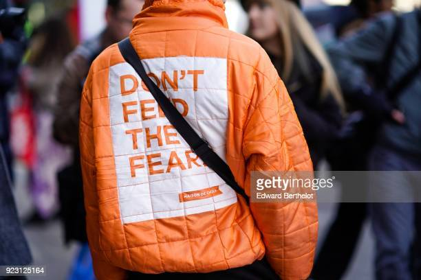 A guest wears an orange puffer coat with the print 'don't feed the fear' during London Fashion Week February 2018 on February 16 2018 in London...