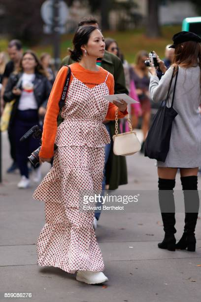 A guest wears an orange pull over a ruffle dress white shoes holds a canon camera outside Mugler during Paris Fashion Week Womenswear Spring/Summer...
