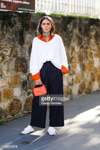 Guest wears an orange shirt, a white wool pullover, an orange bag, navy blue striped pants, white shoes, a striped scarf, outside Loewe, during Paris...