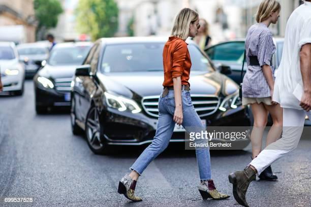 A guest wears an orange silk shirt blue denim jeans pants and snake print shoes outside the Haider Ackermann show during Paris Fashion Week Menswear...