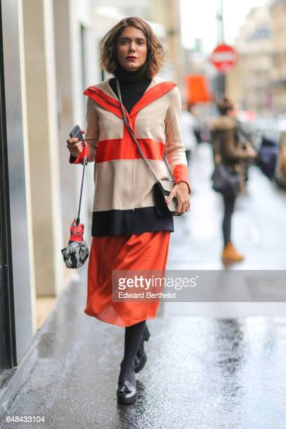 A guest wears an orange skirt and a Gucci bag outside the Valentino show during Paris Fashion Week Womenswear Fall/Winter 2017/2018 on March 5 2017...