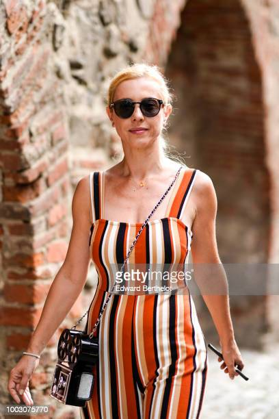 A guest wears an orange striped jumpsuit a bag in the form of a film camera during Feeric Fashion Week 2018 on July 21 2018 in Sibiu Romania