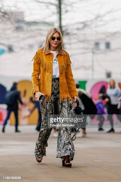 A guest wears an orange suede jacket with fringes floral print flare pants sunglasses during London Fashion Week February 2019 on February 16 2019 in...