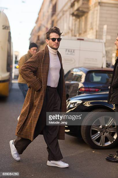 A guest wears an orange tartan plaid overcoat over a white turtleneck brown trousers and white sneakers during Milan Men's Fashion Week Fall/Winter...