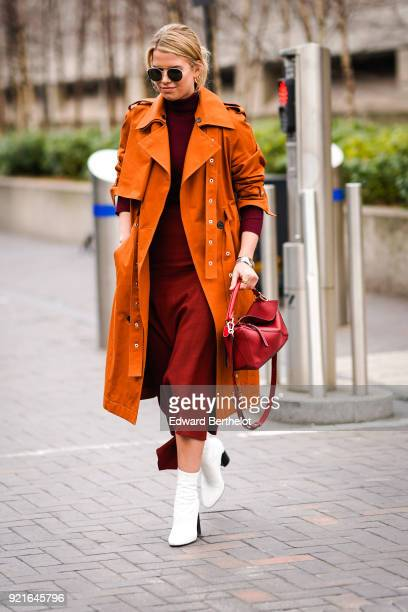 A guest wears an orange trench coat a red dress a red bag white shoes during London Fashion Week February 2018 on February 18 2018 in London England