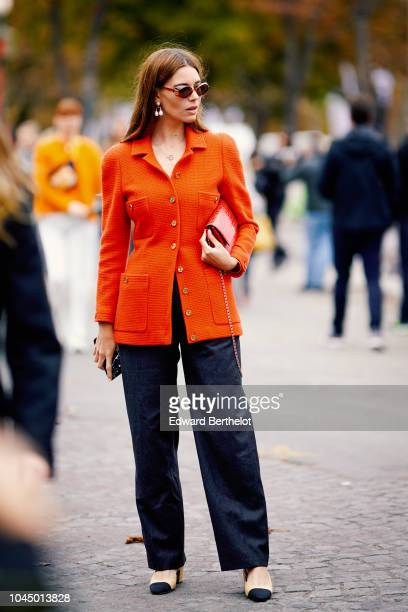 A guest wears an orange tweed jacket outside Chanel during Paris Fashion Week Womenswear Spring/Summer 2019 on October 2 2018 in Paris France