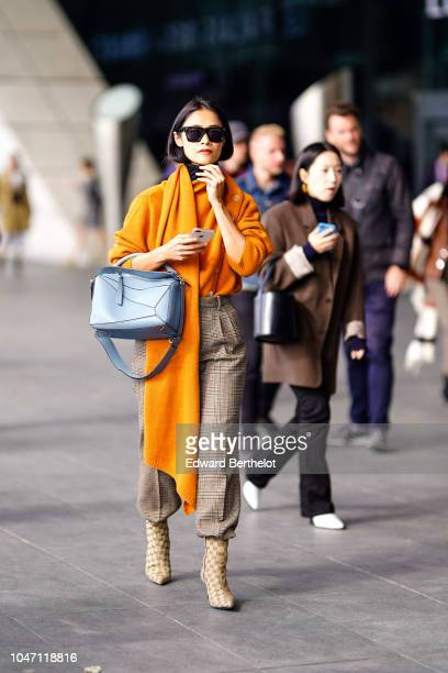 A guest wears an orange wool pullover with integrated scarf gray checked pants a blue bag Gucci monogram boots outside Giambattista Valli during...