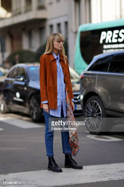 Guest wears an orange/brown suede jacket, a blue striped shirt, blue denim jeans, black shoes, a multicolor scarf with printed patterns, outside...