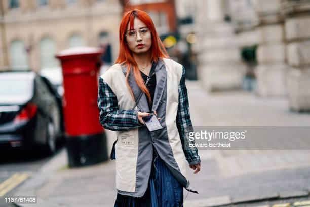 A guest wears an oversize ripped hem grey jacket with white inserts and dark blue and green checkered sleeves a shiny dark blue pleated satin skirt...