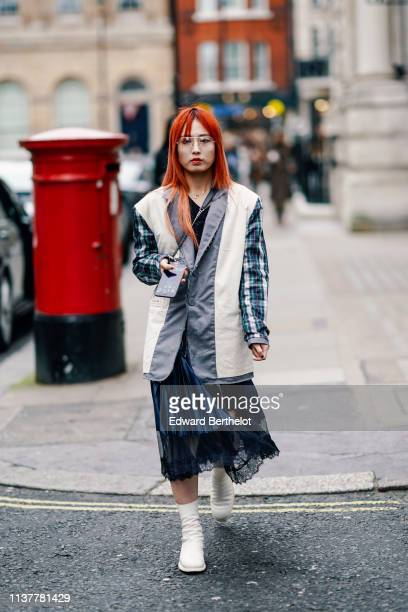 A guest wears an oversize ripped hem grey jacket with white inserts and dark blue and green checkered sleeves a shiny dark blue pleated satin and...