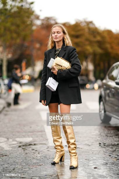 Guest wears an oversized blazer black jacket, a golden Chanel bag, golden Chanel shiny high boots, a black dress, outside Chanel, during Paris...