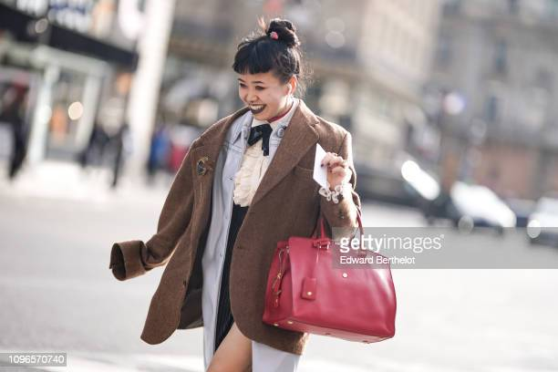 A guest wears an oversized blazer brown jacket a red leather bag outside Berluti during Paris Fashion Week Menswear F/W 20192020 on January 18 2019...