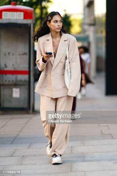A guest wears an oversized blazer jacket flare pants shoes earrings hairclip during London Fashion Week September 2019 on September 13 2019 in London...