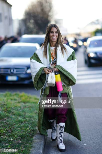 Guest wears an oversized puffer coat with large flare pagoda sleeves, a white bag, purple pants, white leather boots, outside Prada, during Milan...