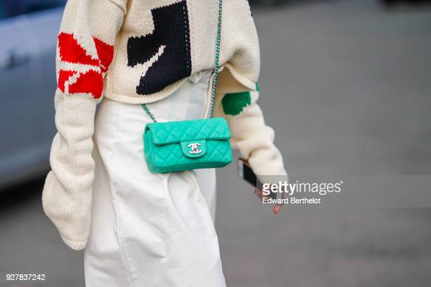 A guest wears an oversized pull over with colored prints a green Chanel bag white flare pants during Paris Fashion Week Womenswear Fall/Winter...