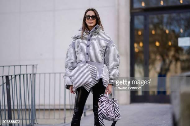 A guest wears an oversized striped puffer coat sunglasses black pants white shoes outside Giambattista Valli during Paris Fashion Week Womenswear...