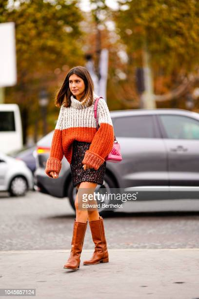 A guest wears an oversized wool gray and orange turtleneck pullover a glitter skirt brown leather boots outside Chanel during Paris Fashion Week...