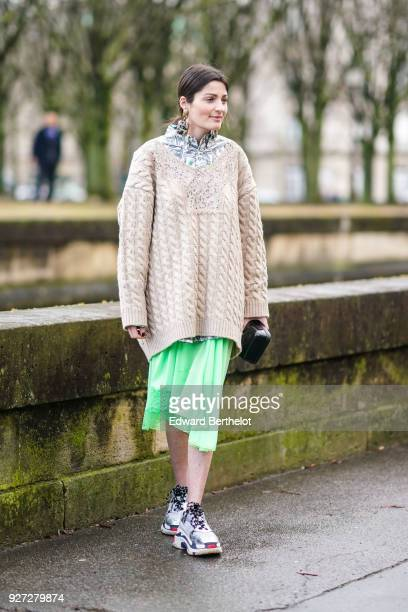 A guest wears an oversized wool pull over a green dress sneakers outside Valentino during Paris Fashion Week Womenswear Fall/Winter 2018/2019 on...