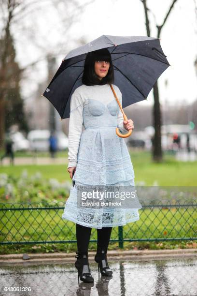 A guest wears an umbrella a lace dress a white pull over black pants and black leather heels outside the Elie Saab show during Paris Fashion Week...