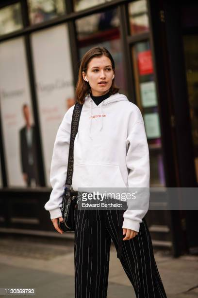 A guest wears Apple airpods a white hooded sweatshirt black pants with thin white stripes during London Fashion Week February 2019 on February 19...