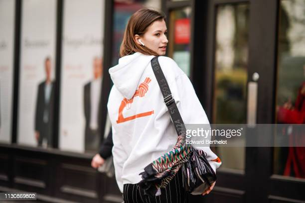 A guest wears Apple Airpods a white hooded sweatshirt with an orange gun impression on the back during London Fashion Week February 2019 on February...