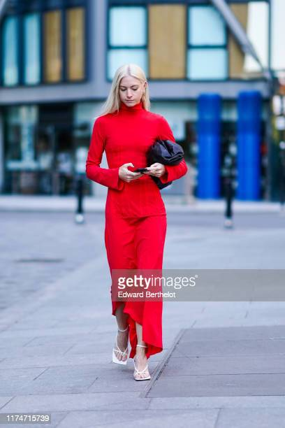 A guest wears ared dress white sandals a black bag during London Fashion Week September 2019 on September 14 2019 in London England