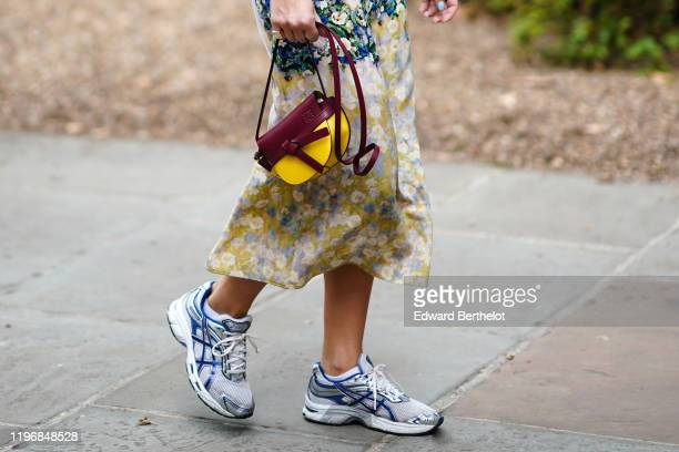 Guest wears Asics blue and gray sneakers, a burgundy and yellow leather Loewe bag, a floral print skirt, during London Fashion Week September 2019 on...