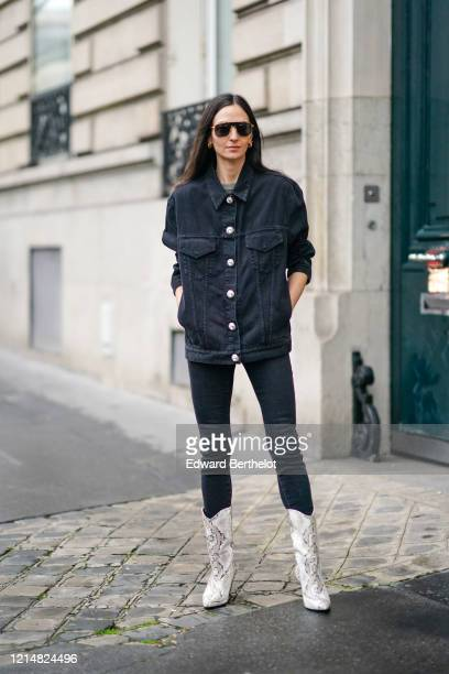 Guest wears aviator sunglasses, a black denim jacket with buttons, black pants, cowboy white boots with snake printed patterns, outside Alessandra...