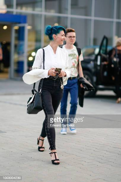A guest wears balck denim pants black shoes a bag a white shirt with flared sleeves during Feeric Fashion Week 2018 on July 20 2018 in Sibiu Romania