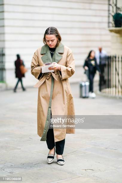 A guest wears beige and green trench coat during London Fashion Week September 2019 on September 16 2019 in London England