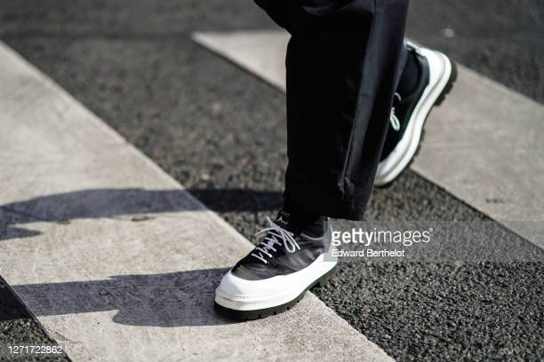 Guest wears black and white Bally shoes, outside Berluti, during Paris Fashion Week - Menswear F/W 2020-2021 on January 17, 2020 in Paris, France.