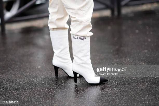 A guest wears black and white Chanel boots 'Gabrielle Chanel Coco' outside Miu Miu during Paris Fashion Week Womenswear Fall/Winter 2019/2020 on...