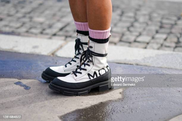 Guest wears black and white leather boots with thick soles, pink wool socks, outside Chanel, during Paris Fashion Week - Womenswear Spring Summer...