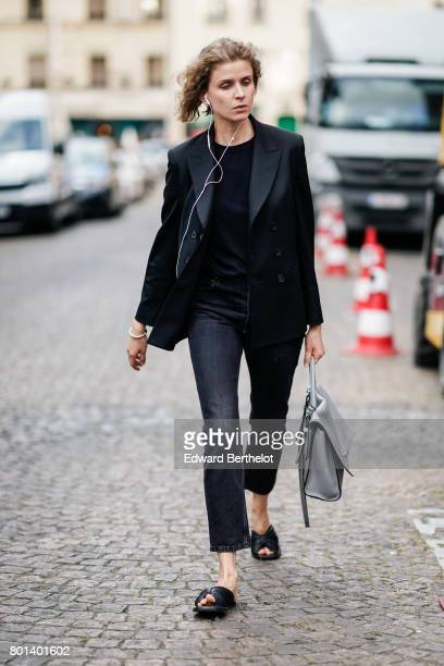 A guest wears black blazer jacket a black top black pants a gray bag outside the Kenzo show during Paris Fashion Week Menswear Spring/Summer 2018 on...