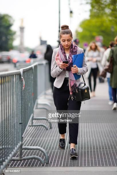 A guest wears black earrings a light grey jacket a pink and purple floral print scarf black pants a black alligator pattern bag black moccasins...