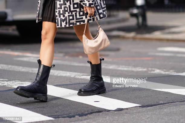 A guest wears black leather boots and a Prada bag outside Longchamp during New York Fashion Week FallWinter 2020 on February 08 2020 in New York City