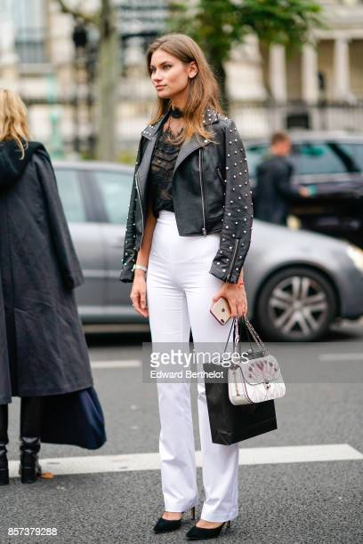 A guest wears black leather jacket white pants a bag outside Shiatzy Chen during Paris Fashion Week Womenswear Spring/Summer 2018 on October 2 2017...