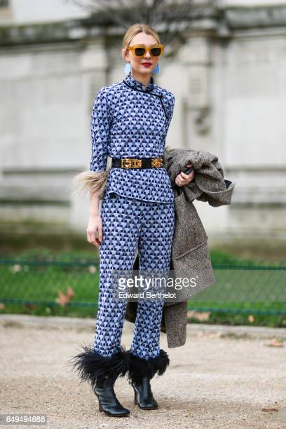 A guest wears black leather shoes with fur a full outfit with black and blue patterns a belt outside the Chanel show during Paris Fashion Week...