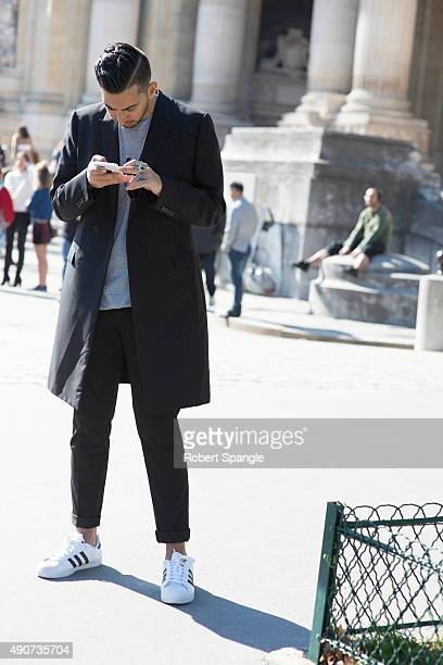 Guest wears black overcoat oversized grey tshirt native american jewelry and Adidas sneakers after Guy Laroche at the Grand Palais during Paris...