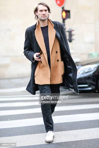 Guest wears black pants, white shoes, a brown jacket, a black top, and black coat, outside the JOUR/NE show, during Paris Fashion Week Womenswear...