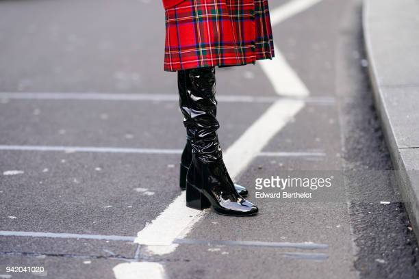 A guest wears black pvc shiny boots during London Fashion Week February 2018 on February 16 2018 in London England