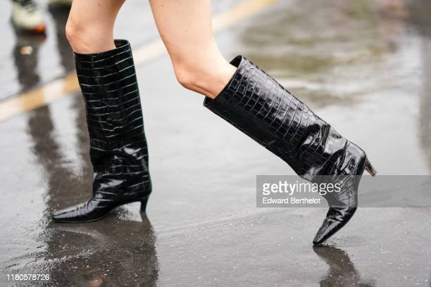 Guest wears black shiny crocodile skin pattern leather boots, outside Chanel, during Paris Fashion Week - Womenswear Spring Summer 2020, on October...