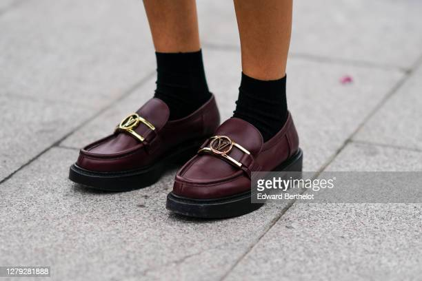 Guest wears black socks and Vuitton golden logo burgundy leather shoes, outside Louis Vuitton, during Paris Fashion Week - Womenswear Spring Summer...