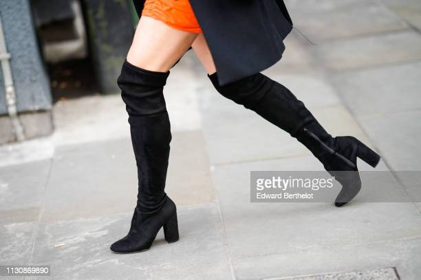 A guest wears black suede kneehigh boots during London Fashion Week February 2019 on February 19 2019 in London England
