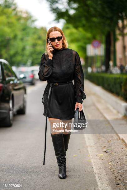 Guest wears black sunglasses, a black short dress with transparent puff sleeves, a black leather belt, a black shiny leather crocodile pattern...