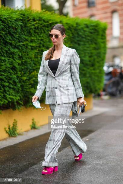 Guest wears black sunglasses, a black tank-top, a pale gray oversized checkered blazer jacket, matching pale gray oversized checkered flared pants,...