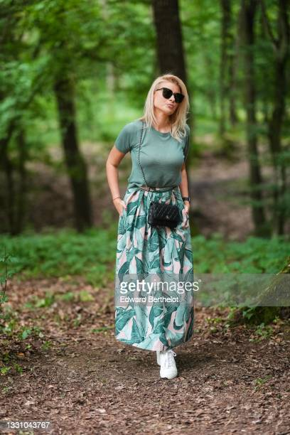 Guest wears black sunglasses, a gold chain necklace, a green t-shirt, a green / pink / pale green long pleated skirt, a black watch, a black shiny...