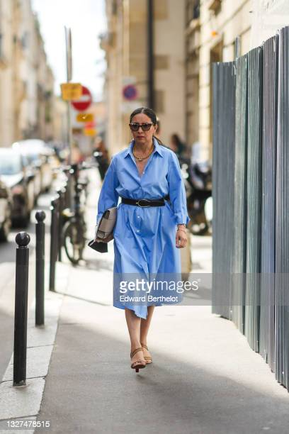 Guest wears black sunglasses, a gold sunglasses chain, a gold chain necklace, a blue long oversized shirt dress, a black leather belt, a silver...